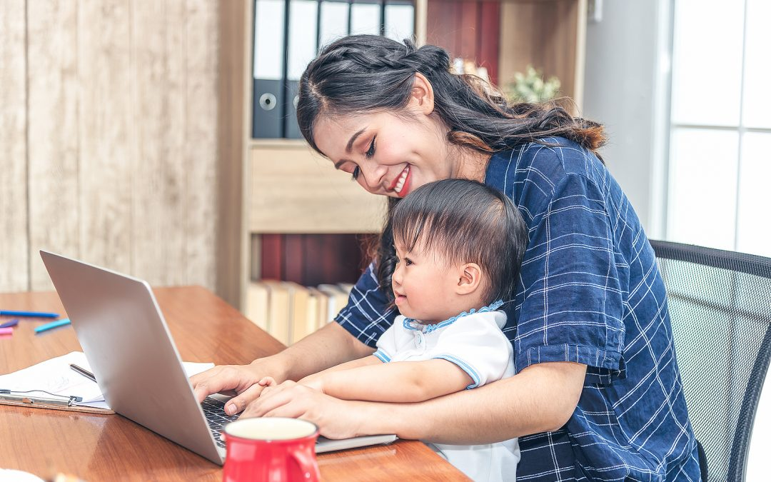 Young Mom Working At Home On A Laptop Computer Whi