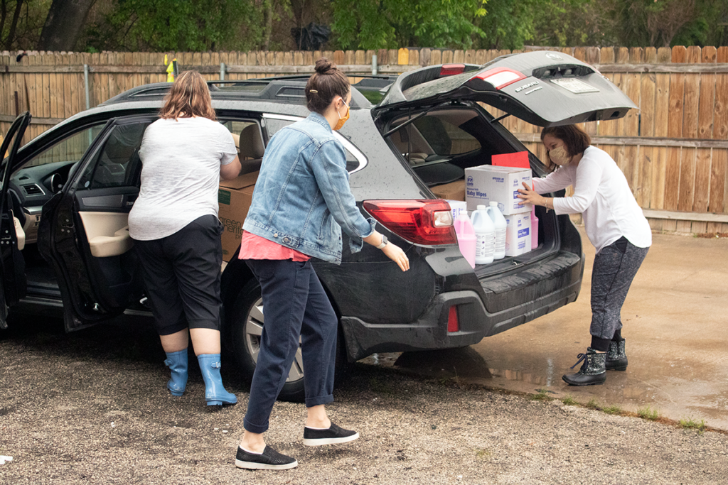 Child Care Services staff load cleaning supplies in a provider's car